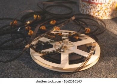 Old-school reel of uncoiled film is lying on the floor on carpet in side warm light of lamp, with caramel popcorn scattered around it, close up. Traditional attributes of watching movies