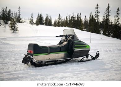 Old-school snow mobile in winter landscape