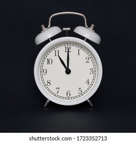 Old-style alarm clock, black and white, it's eleven oclock.