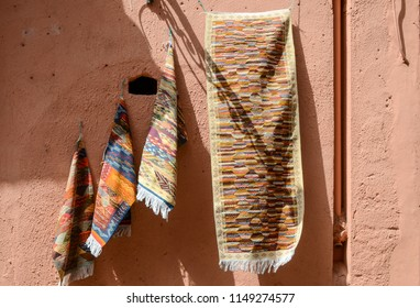 Old-style carpets hang on pink wall in city of Marrakesh