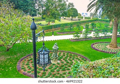 The old-style streetlight covered with the pattern of metal lace, with the flower beds of Bahai garden on the background, Haifa, Israel.