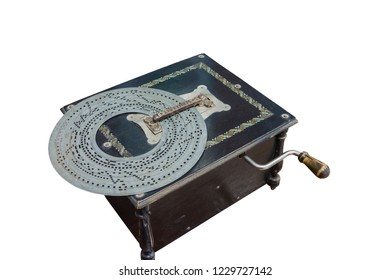 Old-time music box in a black wooden box with perforated metal disc on a white background.