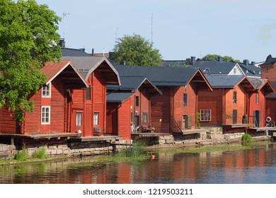 Old-time red wooden barns on the Porvonjoki river on a sunny July afternoon. Porvoo, Finland