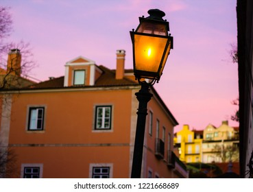 Oldvintage lamppost by nightfall in Lisbon, Portugal. Brightly colored buildings and pink evening sky are on the background.