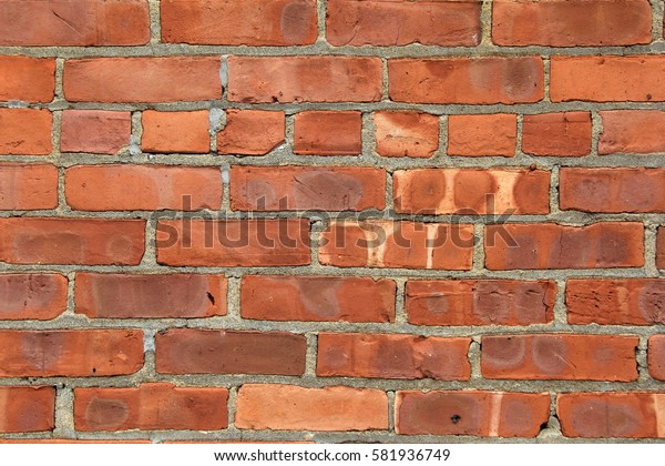 Old,weathered red brick background with uneven shapes and sizes of brick