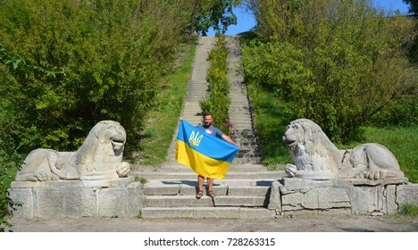 OLESKO UKRAINE 09 1417:Man waving Ukrainia flag at the Olesko Castle is located within the borders of the present-day Busk Raion in Ukraine. Olesko Castle, oval in shape, stands on top of a small hill