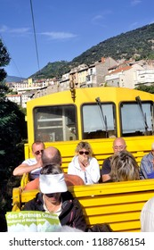OLETTE, FRANCE - SEPTEMBER 4, 2018: The travelers of the little yellow train of the Pyrenees in the wagon in the open air from the station of Olette