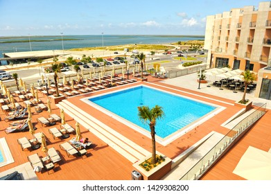Olhao, Portugal - May 30, 2011: Beautiful swimming pool of the Real Marina Hotel with the Ria Formosa Natural Park in the background. Algarve region south of Portugal