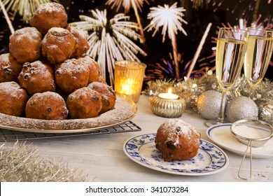 'Oliebollen', traditional Dutch pastry for New Year's Eve. With champagne and fireworks in the background.