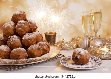 'Oliebollen', traditional Dutch pastry for New Year's Eve. With champagne and sparklers in the background.