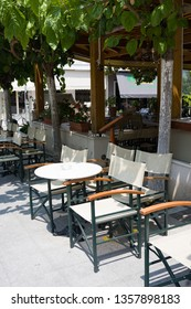 OLIMPIA, GREECE - JUNE 13, 2014: Street cafe with white tables and chairs in Olimpia