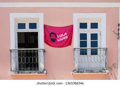 """Olinda, Brazil - Circa April 2019: Red flag with """"Lula Free"""" written in Portuguese on the facade of a house. Lula is an ex-president of Brazil who is currently in jail."""