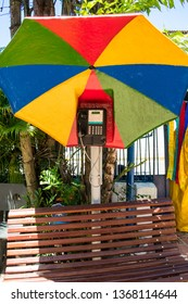 Olinda, Brazil - Circa April 2019: Public pay phone decorated with a colorful umbrella typical from Pernambuco in the historic center of Olinda