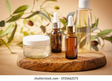 Olive based cosmetic serum, cream and water with sprig of olives on a pastel background