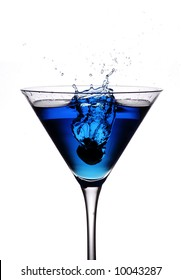 an olive being dropped from height into a blue cocktail