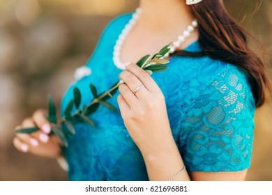 Olive branch in female hands. Hands of the bride. Wedding in Montenegro