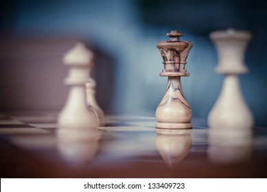 Olive made Chess King isolated with focus on a chess board