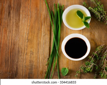 Olive oil, balsamic vinegar and herbs on a vintage wooden background from above.