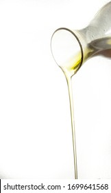 Olive oil being poured from a carafe with white background