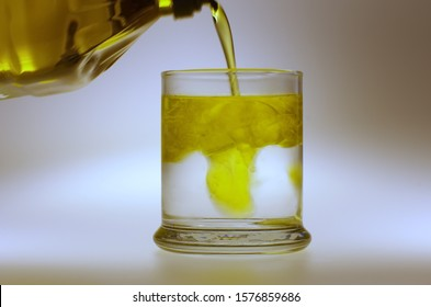 Olive oil being poured into water isolated on white
