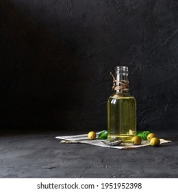 Olive oil bottle on paper with olives and a spoon on a black background with space for text.