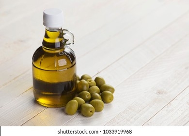 Olive oil in bottle on wooden white surface