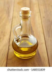 Olive oil in bottle over wooden background