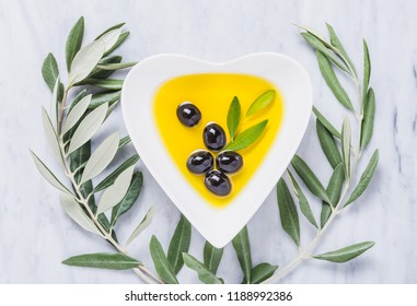 Olive oil bowl and fresh branch of olives on white marble. Testing fresh mediterranean extra virgin olive oil.