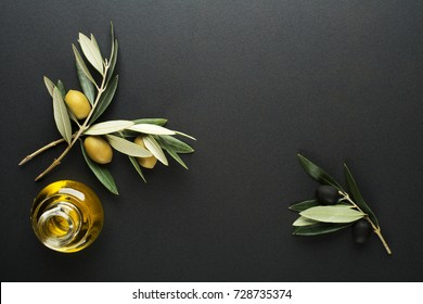 Olive oil and olive branch on black background