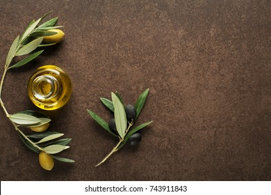 Olive oil and olive branch on brown background