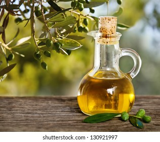 Olive oil and olive branch on the wooden table over nature background