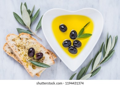 Olive oil and bread fresh branch of olives on white marble background directly above.Testing fresh olive oil.