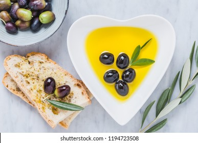 Olive oil and bread on white marble. Testing fresh mediterranean extra virgin olive oil.