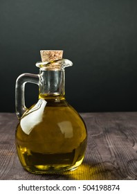 olive oil container bottle with stopper on wood table background, concept of diet and nutrition
