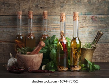 Olive oil with different spices and herbs on a old wooden table.