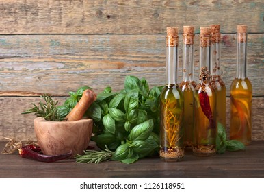 Olive oil with different spices and herbs on a old wooden table. Bottles of olive oil  with basil and wooden mortar.
