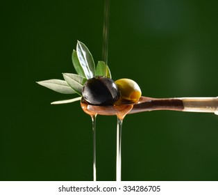 Olive oil falling on two olive with olive leaves to flavor a Mediterranean salad .Typical dish of the Mediterranean diet