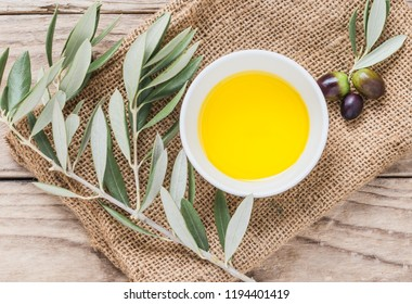 Olive oil and fresh branch with olives on wooden table.