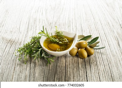 Olive oil with fresh herbs and spices on wooden background