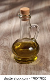 Olive oil in a glass bottle on a wooden table