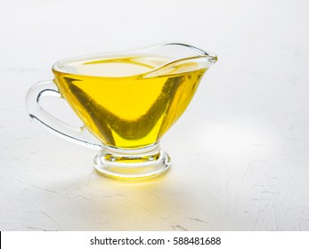 Olive oil in gravy boat on trendy white textured concrete background. Cooking oil in glass jug with copy space