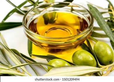 Olive oil. Greek olive oil in glass transparent bowl with olive branches with leaves and olives. Close up on white surface.