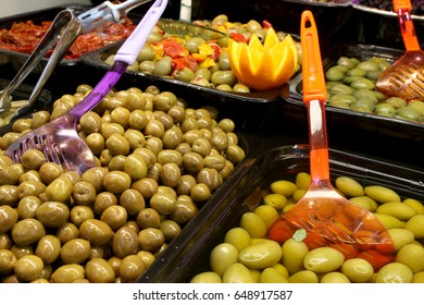 Olive in oil in a grocery bar. Containers with different kinds of italian olives.