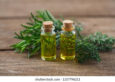 olive oil with herbs on wooden surface