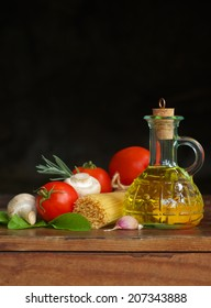 Olive oil and ingredients of Italian cuisine in an old wooden table. fresh vegetables and spaghetti.  Dark background. Mediterranean food.