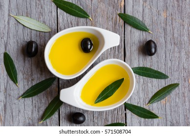 Olive oil with olive leaves on wooden table