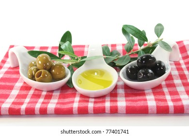 Olive oil with olives and olive branch served in bite spoons