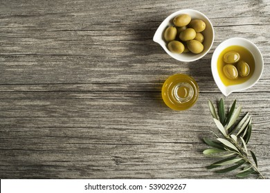 Olive oil with olives fruits on wooden background.