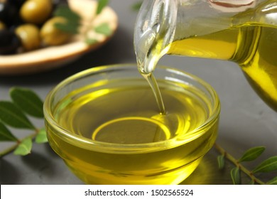 Olive oil, olives and green leaves.