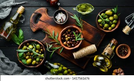 Olive oil and olives on a black wooden background.